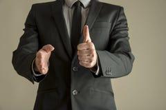 Affärsmannen i den dräkten som gör tummar gör en gest upp Royaltyfri Bild