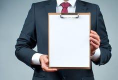 Affärsmannen i dräkt är den hållande skrivplattan arkivfoto