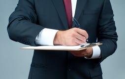 Affärsmannen i dräkt är den hållande skrivplattan och pennan royaltyfria foton