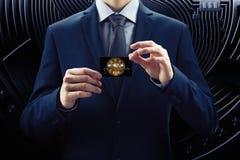 Affärsmannen i dräkt och slipsen rymmer kreditkorten, med cryptocurrency Mynt för bit för begreppskvarterkedja av e-affären royaltyfri fotografi