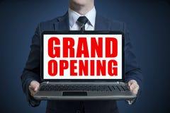 Affärsmannen i en blå dräkt visar en bärbar dator med en STORSLAGEN ÖPPNING för inskrift på en skärm Begrepp för storslagen öppni royaltyfria foton