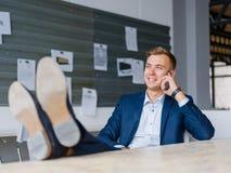 Affärsmannen i en dräkt och en hud skor samtal på en telefon på en suddig bakgrund Förtroendebegrepp Arkivfoton