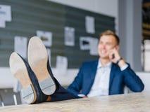 Affärsmannen i en dräkt och en hud skor samtal på en telefon på en suddig bakgrund Förtroendebegrepp Fotografering för Bildbyråer