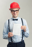 Affärsmannen i en hjälm visar det tomma arket av notepaden royaltyfri bild
