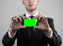 Affärsmannen i en svart dräkt och smoking som rymmer ett kort, en hand som rymmer ett kort, det gröna kortet, kort sätts in, den  Royaltyfri Fotografi