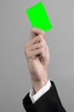 Affärsmannen i en svart dräkt och smoking som rymmer ett kort, en hand som rymmer ett kort, det gröna kortet, kort sätts in, den  Arkivbild