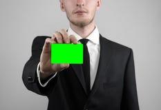Affärsmannen i en svart dräkt och smoking som rymmer ett kort, en hand som rymmer ett kort, det gröna kortet, kort sätts in, den  Arkivfoto