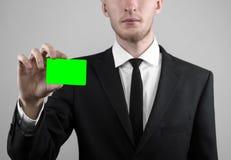 Affärsmannen i en svart dräkt och smoking som rymmer ett kort, en hand som rymmer ett kort, det gröna kortet, kort sätts in, den  Royaltyfri Bild