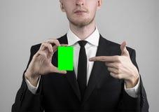 Affärsmannen i en svart dräkt och smoking som rymmer ett kort, en hand som rymmer ett kort, det gröna kortet, kort sätts in, den  Royaltyfri Foto