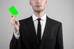Affärsmannen i en svart dräkt och smoking som rymmer ett kort, en hand som rymmer ett kort, det gröna kortet, kort sätts in, den  Arkivbilder