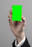 Affärsmannen i en svart dräkt och smoking som rymmer ett kort, en hand som rymmer ett kort, det gröna kortet, kort sätts in, den  Arkivfoton