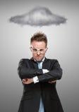 Affärsmannen i exponeringsglas står under det stormiga molnet Arkivbild