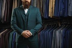 Affärsmannen i klassisk väst mot rad av dräkter shoppar in Royaltyfri Foto