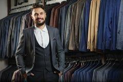 Affärsmannen i klassisk väst mot rad av dräkter shoppar in Arkivbild