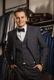 Affärsmannen i klassisk väst mot rad av dräkter shoppar in En ung stilfull man i ett svart torkdukeomslag Det är i visningslokale Royaltyfri Foto