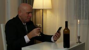 Affärsmannen i restaurangtext genom att använda mobilen och läppjar ett exponeringsglas med vin arkivfilmer