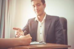 Affärsmannen inviterar partnern att underteckna ett affärsavtal Arkivbild