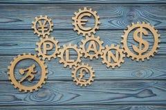 Affärsmannen kör ett pussel i kugghjulet med ordet PLAN och symboler av pengardollar, euroet, yen, pund ett pund sterling Royaltyfri Foto