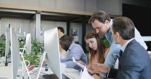 Affärsmannen kommer att hjälpa affärsfolk att handla med dokument som arbetar i idérikt kontorsutrymme, kollegateamwork stock video