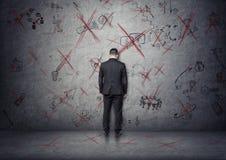 Affärsmannen lutar hans panna till betongväggen med visade idéer som korsade vid rött Arkivfoto