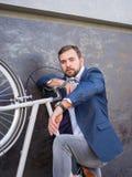 Affärsmannen lyftte hans vita cykel och stod Royaltyfri Foto