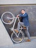 Affärsmannen lyftte hans vita cykel och stod Arkivbild