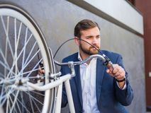 Affärsmannen lyftte hans vita cykel och stod Royaltyfria Bilder