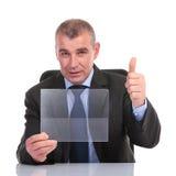 Affärsmannen med den genomskinliga panelen visar upp tummen Arkivfoton