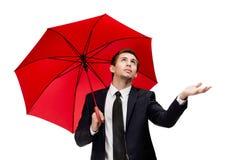 Affärsmannen med det öppnade paraplyet kontrollerar regnet Fotografering för Bildbyråer