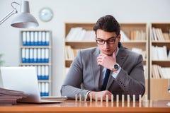 Affärsmannen med domino i kontoret Arkivbilder