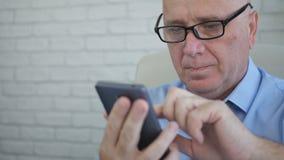 Affärsmannen med glasögon smsar genom att använda mobiltelefonen royaltyfri fotografi