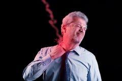 Affärsmannen med halsen smärtar som blixtar Royaltyfria Bilder
