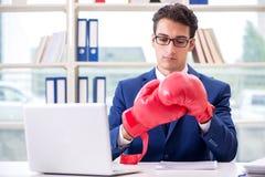 Affärsmannen med ilskna boxninghandskar i regeringsställning arkivbilder