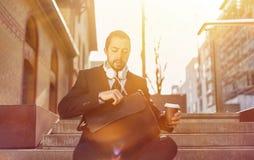Affärsmannen med kaffe rånar för att gå på gå arkivfoton
