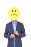 Affärsmannen med ledsen smiley vände mot ballongen på kontorsskrivbordet Fotografering för Bildbyråer
