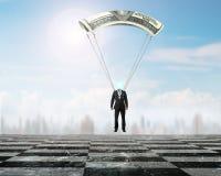 Affärsmannen med pengar hoppa fallskärm landning på schackbrädejordning Royaltyfri Fotografi