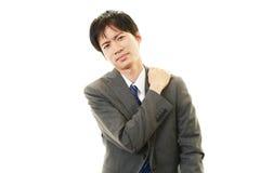 Affärsmannen med skuldran smärtar. arkivfoto