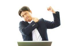 Affärsmannen med skuldran smärtar. arkivfoton