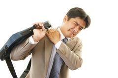 Affärsmannen med skuldran smärtar. royaltyfria foton