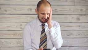 Affärsmannen med smartphonen tycker om dåliga nyheter stock video