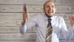 Affärsmannen med smartphonen tycker om goda nyheter stock video