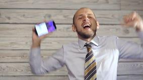 Affärsmannen med smartphonen tycker om goda nyheter lager videofilmer