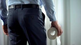 Affärsmannen med toalettpapper i handlidande från hemorrhoid smärtar, diarrén royaltyfri fotografi