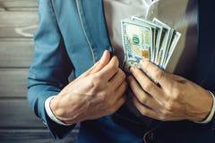 Affärsmannen, medlemmen eller tjänstemannen sätter en muta i hans fack arkivfoton