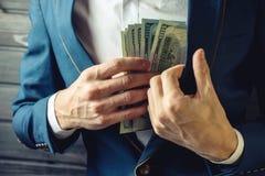 Affärsmannen, medlemmen eller tjänstemannen sätter en muta i hans fack arkivbild
