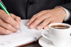 Affärsmannen noterar hans idé till dagboken Arkivfoto