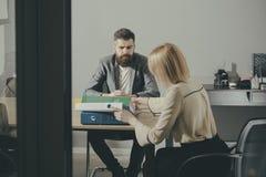 Affärsmannen och affärskvinnan sitter på kontorsskrivbordet Den skäggiga mannen och kvinnan har affärsmöte Koncentration på arbet arkivbild