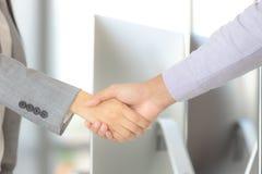 Affärsmannen och affärskvinnan skakar händer för jobb för arbete tillsammans arkivfoto