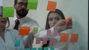 Affärsmannen och businesswonen klibbar anmärkningar på exponeringsglas, medan diskutera dem arkivfilmer