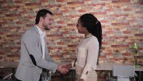 Affärsmannen och den afro amerikanska kvinnan för affär skakar händer i regeringsställning arkivfilmer